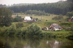 Den tunga grå färgen fördunklar i den kalla hösthimlen över by med små hus som är långväga i bergen och fälten Små flodflöden royaltyfri foto