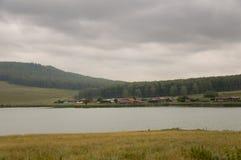 Den tunga grå färgen fördunklar i den kalla hösthimlen över by med små hus som är långväga i bergen och fälten Små flodflöden arkivbilder