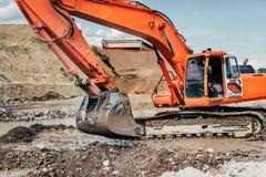 Den tunga industriella grävskopan som arbetar under earthmoving, fungerar på huvudvägkonstruktionsplatsen arkivfoton