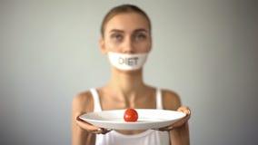 Den tunna flickan med den tejpade muninnehavplattan med tomaten som evakuerar bantar, anorexi fotografering för bildbyråer