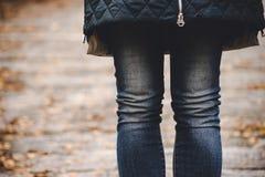 Den tunna kvinnlign lägger benen på ryggen i jeans mot bakgrunden av ett höstlandskap royaltyfria bilder