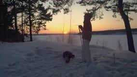 Den turist- flickan dricker te från termoset i snöig vinterskog in på solnedgången arkivfilmer