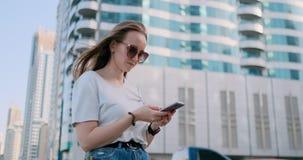 Den turist- flickan i sommaren i Dubai skriver ett meddelande, ser en översikt på smartphonen stock video