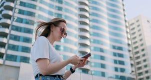 Den turist- flickan i sommaren i Dubai skriver ett meddelande, ser en ?versikt p? smartphonen lager videofilmer