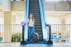 Den turist- flickan med ryggsäcken och bär på bagage i internationell flygplats, på rulltrappan Arkivbilder