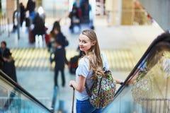 Den turist- flickan med ryggsäcken och bär på bagage i internationell flygplats, på rulltrappan arkivbild