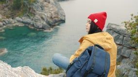 Den turist- flickan som sitter på kanten av en klippa i lagun och, tycker om en härlig sikt lager videofilmer