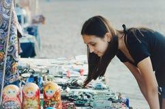 Den turist- flickan undersöker souvenir som säljs på gatan i staden av den Vyborg, Leningrad regionen royaltyfria foton