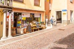 Den turist- gatadelikatessaffären shoppar med traditionella italienska produkter i Cividale del Friuli, Italien fotografering för bildbyråer
