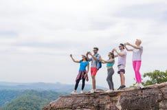 Den turist- gruppen med ryggsäcken tar fotoet av landskapet från bergöverkant på den cellSmart telefonen royaltyfri foto