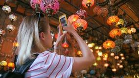 Den turist- kvinnan som gör fotoet med smartphonen i souvenir, shoppar med traditionella turkiska lampor stock video