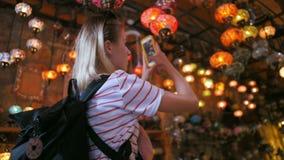 Den turist- kvinnan som gör fotoet med smartphonen i souvenir, shoppar med traditionella turkiska lampor lager videofilmer