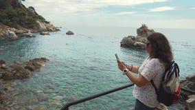 Den turist- kvinnan tar bilder av att förbluffa landskap med havet vid smartphonen stock video