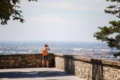 Den turist- mannen står med hans baksida på visningplattformen i Bergamo i Italien och tar ett foto på de bärande kortslutningarn royaltyfri foto