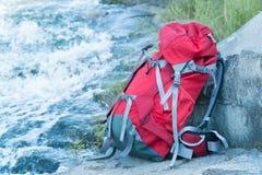 Den turist- ryggsäcken står nära en bergflod arkivfoton