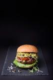 Den Turkiet hamburgaren med pestosås och kryddkrassesallad på den svarta stenen stiger ombord Royaltyfri Foto