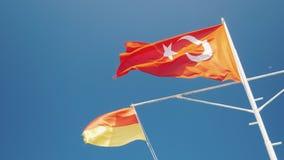 Den turkiska flaggan och flaggan av räddningstjänsten fladdrar mot den blåa himlen Kassaskåpet vilar begrepp arkivfilmer