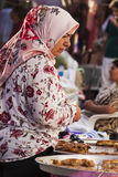 Den turkiska kvinnan köper på basaren Arkivbild