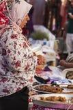 Den turkiska kvinnan köper på den turkiska basaren Arkivfoton