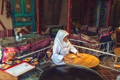 Den turkiska kvinnan rullar degen för att förbereda traditionella turkiska bakelser Royaltyfri Foto