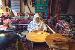 Den turkiska kvinnan rullar degen för att förbereda traditionella turkiska bakelser Arkivbild