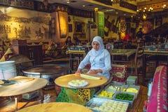Den turkiska kvinnan rullar degen för att förbereda traditionella turkiska bakelser Royaltyfria Bilder