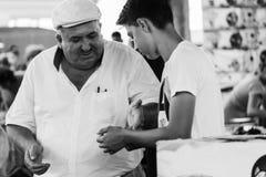 Den turkiska mannen betalar en pojke Royaltyfri Fotografi