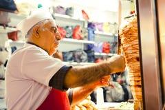 Den turkiska mannen lagar mat och säljer kebab Arkivfoton