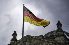 Den tyska flaggan flyger ovanför den Reichstag byggnaden i Berlin Royaltyfria Bilder