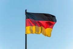 Den tyska flaggan på en pol med blå himmel arkivbilder