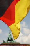 Den tyska flaggan vinkar i förgrunden med den Brandenburg porten i bakgrunden Royaltyfri Foto