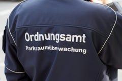 Den tyska tjänstemannen för offentlig beställning/parkerar servicemannen (för säkerhet) Arkivbilder