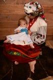 Den ukrainska modern som ammar och kramar henne, behandla som ett barn Fotografering för Bildbyråer
