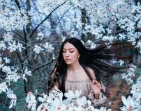 Den underbara attraktiva mörker-haired damen med ögon stängde ställningar i trädgården av att blomma magnolior hår flyger upp med royaltyfri bild