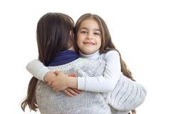 Den underbara flickan kramar hennes moder tillbaka och att le royaltyfria foton