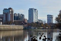Den underbara sikten av det lyxiga bostads- av skyskrapor som är komplexa till och med de gamla träden, husen, reflekteras i vatt royaltyfria bilder