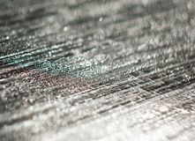 Den unfocused bakgrunden av silveren blänker av vattensmå droppar på svarten royaltyfri foto
