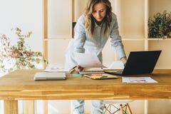Den unga affärskvinnakvinnan är det stående near köksbordet som läser dokument, bruksbärbara datorn, arbete som studerar Royaltyfria Foton
