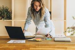 Den unga affärskvinnakvinnan är det stående near köksbordet som läser dokument, bruksbärbara datorn, arbete som studerar Royaltyfri Foto