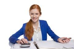 Den unga affärskvinnan är beräknande och handstil på ett papper Arkivbilder