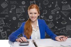 Den unga affärskvinnan är beräknande och handstil på ett papper Arkivfoton