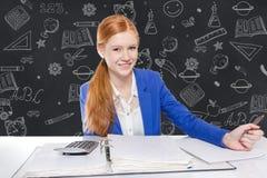Den unga affärskvinnan är beräknande och handstil på ett papper Royaltyfri Foto