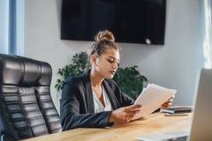 Den unga affärskvinnan är en bra allvarlig flicka som arbetar i kontoret Under detta kontrollerar det dokumenten, genom att grans fotografering för bildbyråer