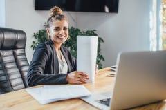 Den unga affärskvinnan är en bra allvarlig flicka som arbetar i kontoret Under detta kontrollerar det dokumenten, genom att grans royaltyfri bild