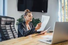Den unga affärskvinnan är en bra allvarlig flicka som arbetar i kontoret Under detta kontrollerar det dokumenten, genom att grans arkivfoton
