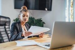 Den unga affärskvinnan är en bra allvarlig flicka som arbetar i kontoret Under detta kontrollerar det dokumenten, genom att grans royaltyfri fotografi