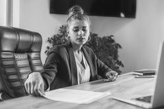 Den unga affärskvinnan är en bra allvarlig flicka som arbetar i kontoret Under detta kontrollerar det dokumenten, genom att grans royaltyfria bilder