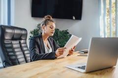Den unga affärskvinnan är en bra allvarlig flicka som arbetar i kontoret Under detta kontrollerar det dokumenten, genom att grans arkivfoto