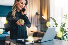 Den unga affärskvinnan är den stående inomhus near tabellen framme av datoren, medan tala på mobiltelefon- och innehaväpplet arkivfoton