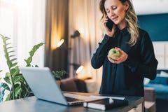 Den unga affärskvinnan är den stående inomhus near tabellen framme av datoren, medan tala på mobiltelefon- och innehaväpplet royaltyfri foto